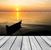 在海滩的木大阳台与清楚的天空和日落的风平浪静 库存照片