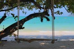 在海滩的木摇摆长凳 免版税库存图片