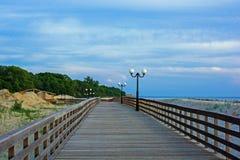 在海滩的木散步与在日落的路灯柱在波罗地 库存照片