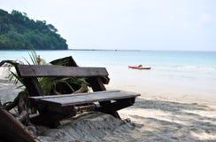 在海滩的木椅子 免版税库存照片