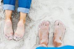 在海滩的桑迪女性和男性脚 免版税库存照片
