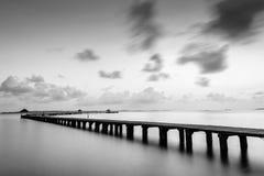 在海滩的桥梁在日出和海挥动 免版税库存图片