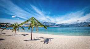 在海滩的棕榈伞在克罗地亚 库存照片
