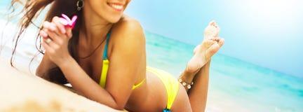 在海滩的横幅华美的晒黑女性身体 免版税库存照片