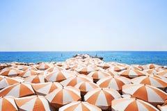 在海滩的橙色伞 免版税库存图片