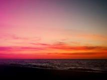 在海滩的橙色和桃红色日落天空 库存照片