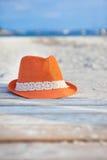 在海滩的橙色帽子 免版税库存照片