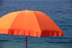 在海滩的橙色遮阳伞 图库摄影