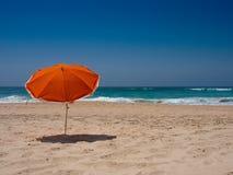 在海滩的橙色遮阳伞 免版税图库摄影