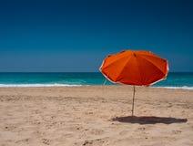 在海滩的橙色遮阳伞 免版税库存图片