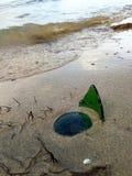 在海滩的残破的瓶 库存图片