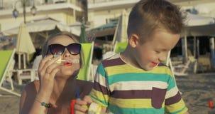 在海滩的母亲和儿童吹的泡影 影视素材