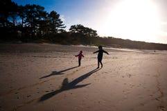 在海滩的母亲和女儿戏剧 免版税图库摄影