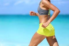 在海滩的母赛跑者与体育胸罩和短裤 库存图片