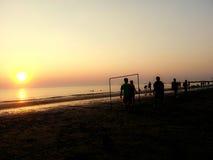 在海滩的比赛:日落 库存图片