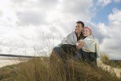 在海滩的毯子包裹的夫妇 免版税库存照片
