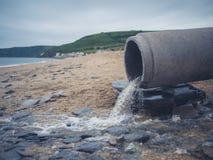 在海滩的污水管子 免版税库存照片