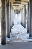 在海滩的汹涛在码头下 图库摄影