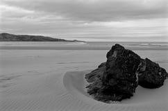 在海滩的沙子压下的岩石 免版税库存照片