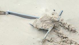 在海滩的沙子固定的重金属的船锚 库存照片