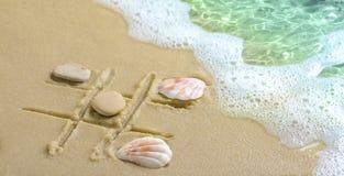 在海滩的沙子画的一场tic TAC脚趾比赛 库存图片