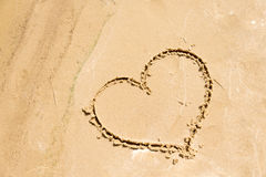 在海滩的沙子画的心脏的形状 背景爱红色玫瑰色符号白色 免版税库存图片