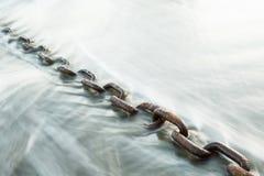 在海洋的波浪的大生锈的链子 免版税库存照片