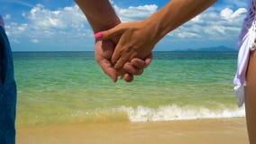 在海滩的浪漫夫妇举行手 影视素材