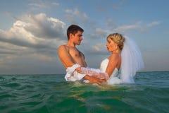 新结婚的夫妇游泳在海 库存图片