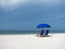 在海滩的海滩睡椅和伞 库存图片