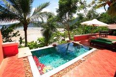 在海滩的游泳池,在庭院旁边的太阳懒人 库存图片