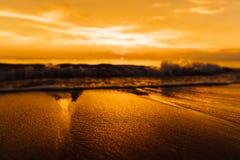 在海滩的湿海沙反对背景金黄日落 在海洋海岸的日落 图库摄影