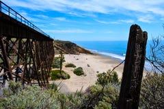 在海滩的火车桥梁 免版税图库摄影