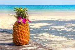 在海滩的热带异乎寻常的菠萝鸡尾酒 库存照片