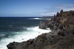 在海洋的熔岩峭壁在兰萨罗特岛 免版税图库摄影