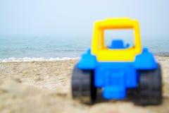 在海滨的玩具拖拉机 免版税库存图片