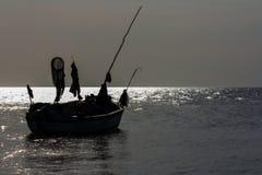 在海洋的现出轮廓的小船 免版税库存照片