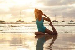 在海滩的瑜伽在日落的水附近 图库摄影