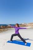 在海滩的瑜伽实践 免版税库存图片