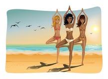 在海滩的瑜伽小组 库存图片