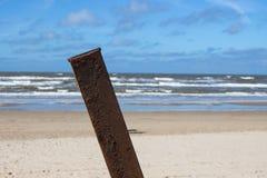 在海滩的生锈的杆 库存图片