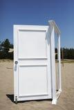 在海滩的白色门 库存照片