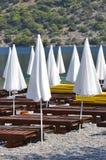 在海滩的白色闭合的遮阳伞 库存图片