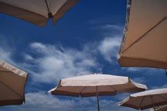 在海滩的白色阳伞在蓝天下 库存照片