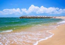 在海滩的石防堤 免版税库存照片