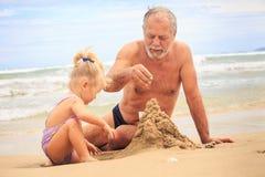 在海滩的祖父小的白肤金发的女孩男孩修造沙子城堡 免版税图库摄影
