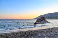 在海滩的秸杆伞在日落期间 免版税库存照片