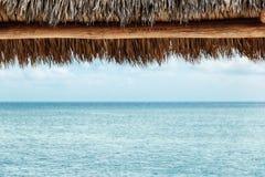 在海滩的秸杆遮篷 免版税库存图片