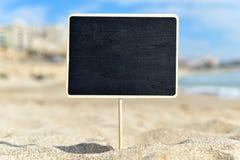 在海滩的空白的黑牌 图库摄影