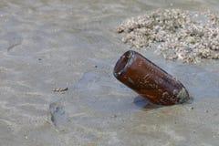 在海滩的空的玻璃瓶 免版税库存图片